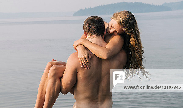 Nude man carrying nude woman into water