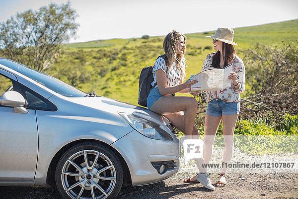 Zwei junge Frauen neben dem Auto  Blick auf die Karte