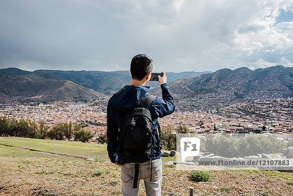 Mann fotografiert Blick aus Sacsayhuaman  mit Smartphone  Cusco  Peru  Südamerika
