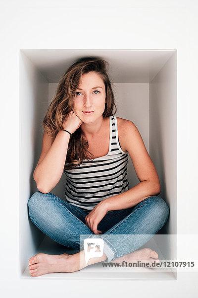 Porträt einer jungen Frau in einer Loge sitzend