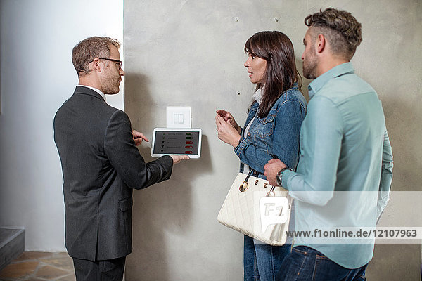 Estate agent standing with couple  using digital tablet to demonstrate technology in new home