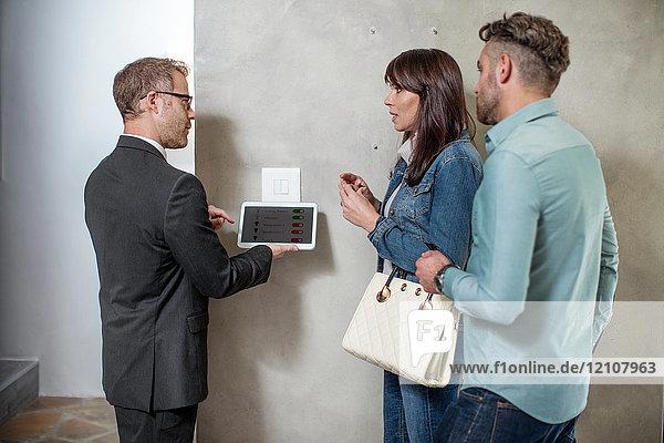 Immobilienmakler steht mit Ehepaar und nutzt digitales Tablett zur Demonstration der Technologie im neuen Zuhause