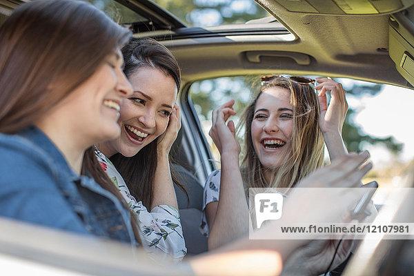 Drei junge Frauen im Auto  lachend