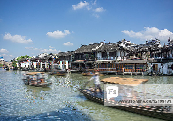 Riverboats on waterway with traditional waterfront buildings  Shanghai  China