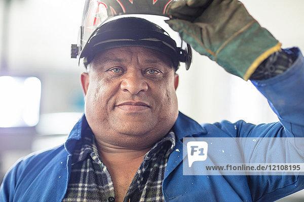 Portrait of mature male car mechanic in welding mask at repair garage