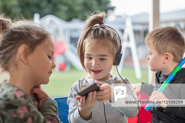 Young girl with friend  holding smartphone  wearing headphones