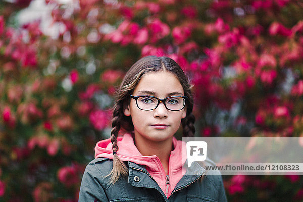 Portrait of girl with plaits and glasses looking at camera