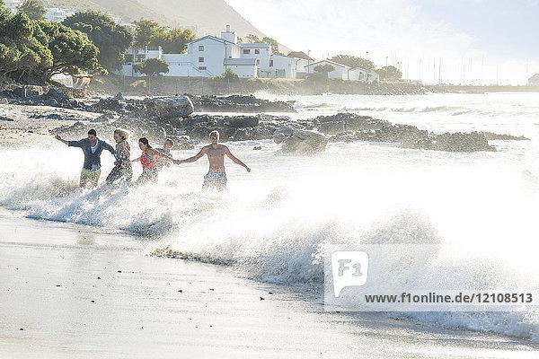 Junge erwachsene Freunde rennen und planschen bei Strandparty durch Wellen