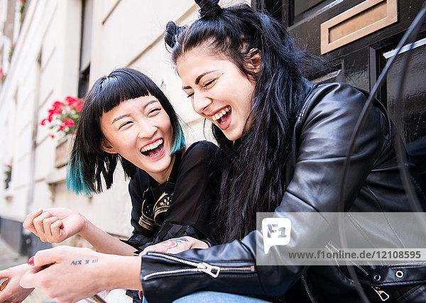 Zwei junge stilvolle Freundinnen sitzen vor der Tür und lachen