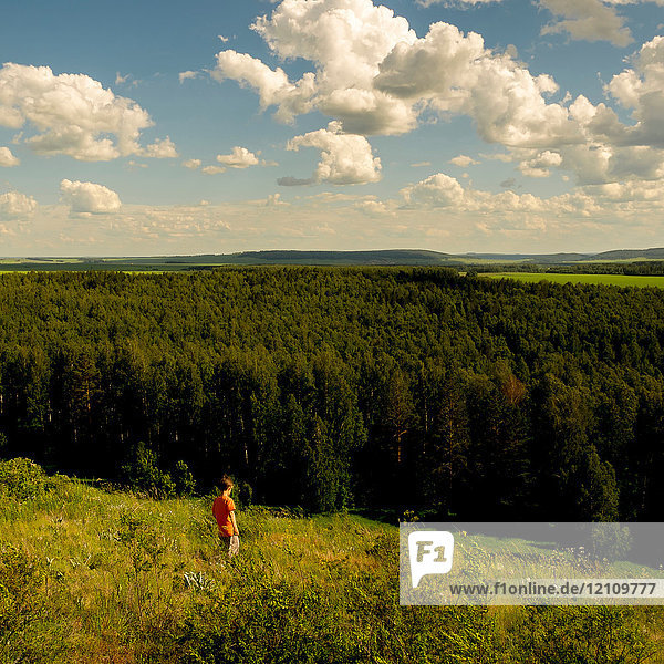 Young boy walking through field  Ural  Chelyabinsk  Russia  Europe