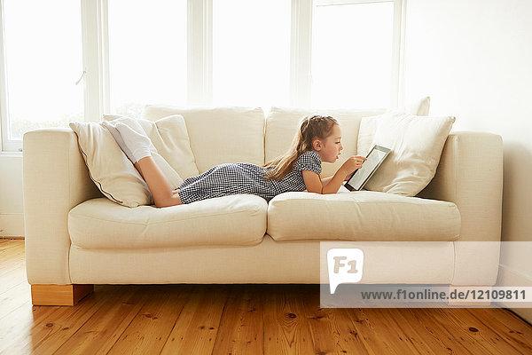Junges Mädchen  entspannt auf dem Sofa  mit digitalem Tablet