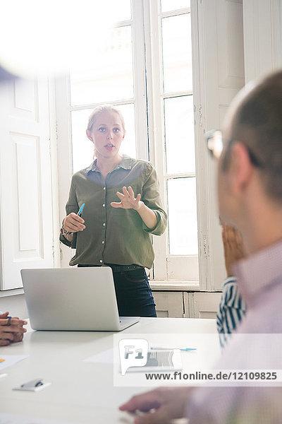 Junge Geschäftsfrau erklärt Präsentation am Vorstandstisch