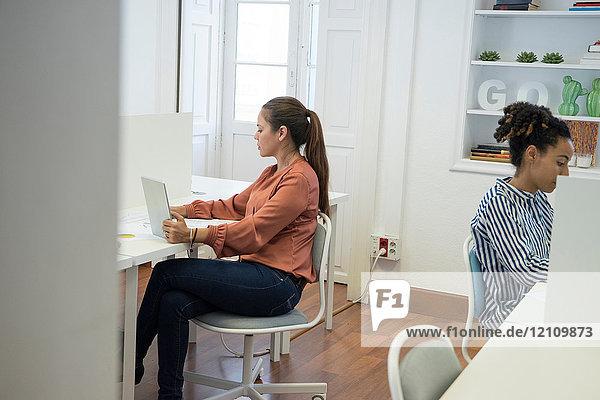Zwei Geschäftsfrauen tippen am Büroschreibtisch auf Laptops