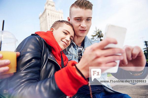 Junges Paar beim Smartphone-Selfie in der Stadt