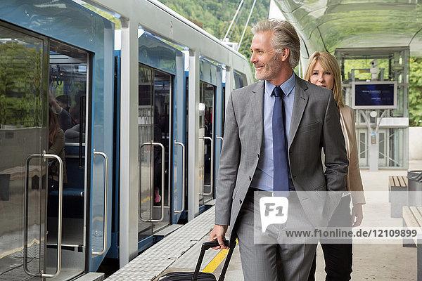 Businessman with suitcase on railway platform
