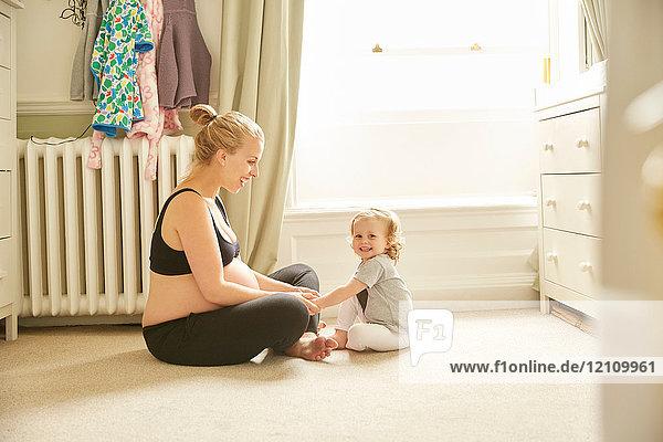 Schwangere Frau und Tochter im Schlafzimmer