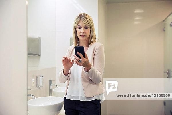Frau benutzt Smartphone im Badezimmer