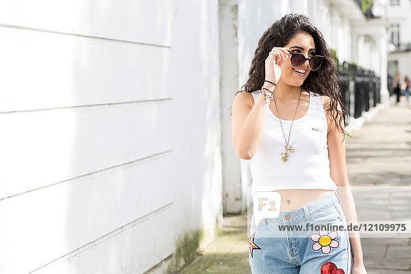 Junge Frau mit langen gewellten Haaren schlendert auf der Straße und schaut über eine Sonnenbrille