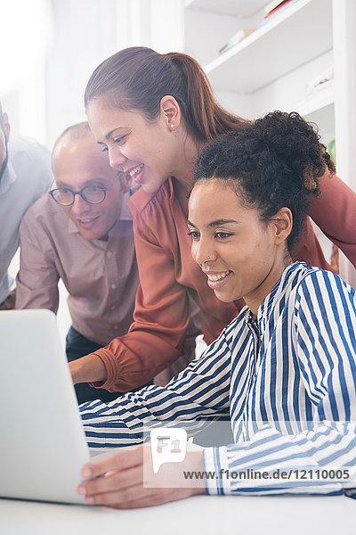 Geschäftsfrauen und -männer schauen auf den Laptop am Konferenztisch