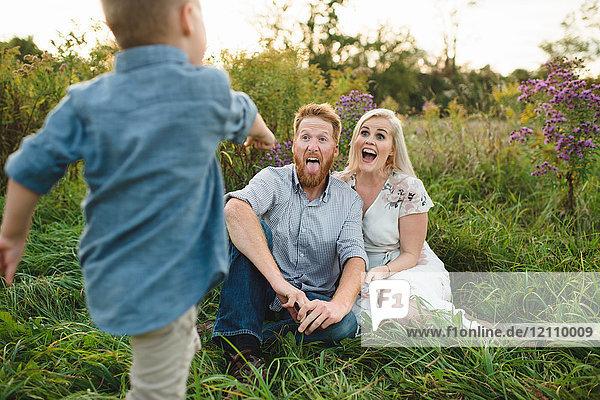 Junge überrascht Eltern,  die im hohen Gras sitzen