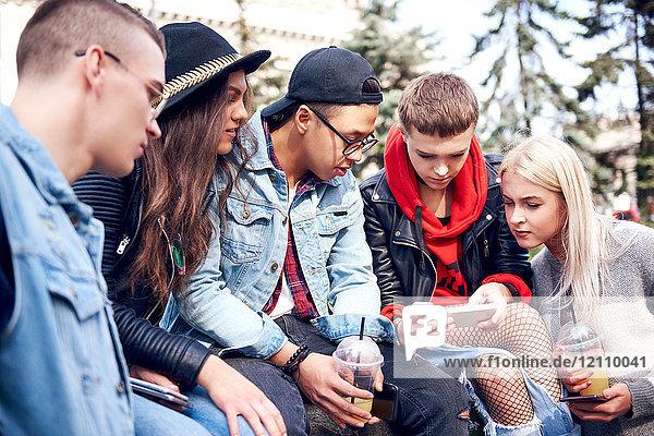 Fünf junge erwachsene Freunde sitzen in der Stadt an der Wand und schauen auf ein Smartphone