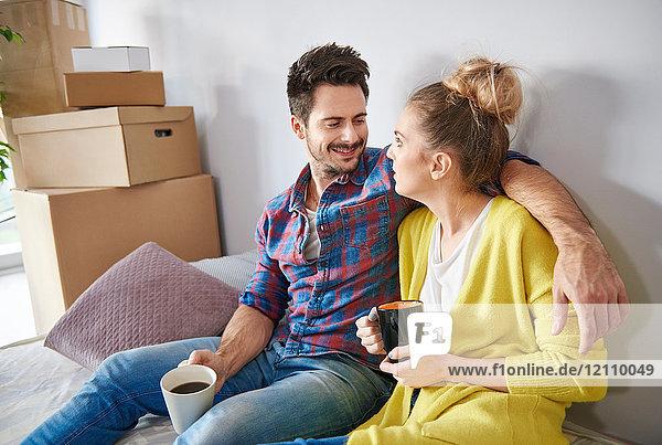Junges Paar zu Hause  umgeben von Pappkartons  Kaffee trinkend  lächelnd