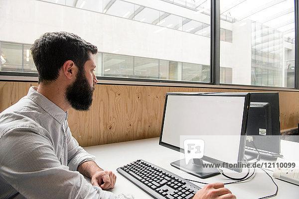 Mann im Büro mit Desktop-Computer