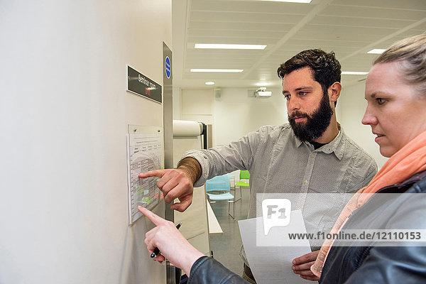 Tutor und Student sehen sich den Stundenplan an der Tür des Seminarraums an