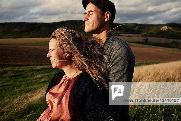 Schwangeres Paar im mittleren Erwachsenenalter auf windigem Hang