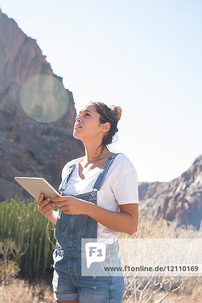 Junge Wanderin mit digitalem Tablett  die vom sonnenbeschienenen Tal aufblickt  Las Palmas  Kanarische Inseln  Spanien