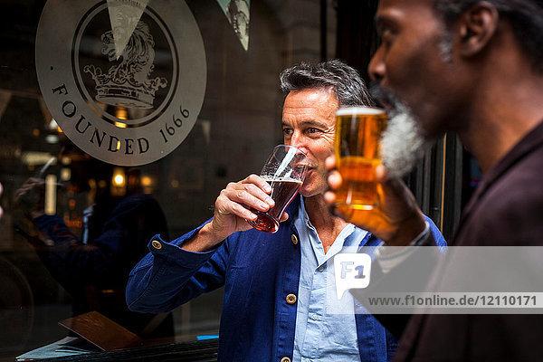 Zwei reife Männer  die vor der Kneipe stehen und Bier trinken