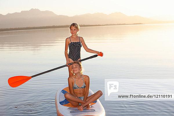 Zwei junge Mädchen paddeln auf dem Wasser