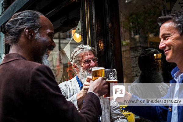 Drei reife Männer  die vor der Kneipe stehen  Biergläser halten und einen Toast ausbringen