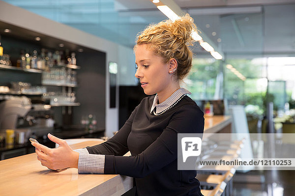 Woman at coffee shop counter using smartphone