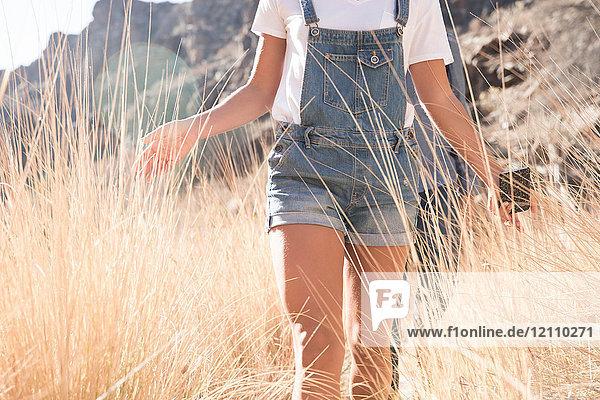 Mittelteil eines jungen Wanderpaares  das beim Wandern im Tal langes Gras berührt  Las Palmas  Kanarische Inseln  Spanien