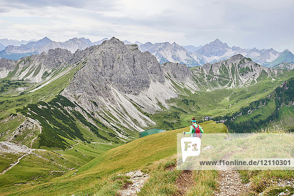 Rear view of female hiker hiking down valley in Tannheim mountains  Tyrol  Austria
