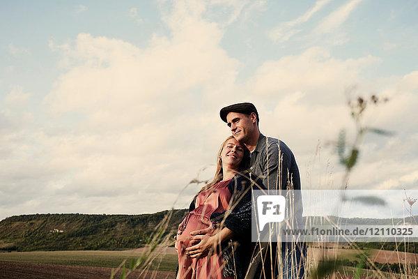 Porträt eines glücklichen schwangeren  mittleren Erwachsenenpaares auf Feldern
