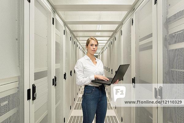 Porträt einer jungen Frau im Datenzentrum  die einen Laptop benutzt