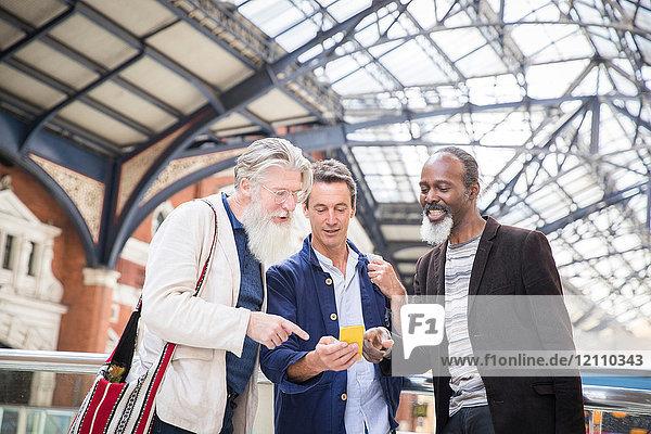 Drei reife Männer am Bahnhof mit Blick auf das Smartphone