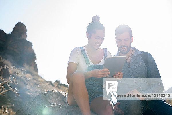 Junges Wanderpaar betrachtet digitales Tablet im sonnenbeschienenen Tal  Las Palmas  Kanarische Inseln  Spanien
