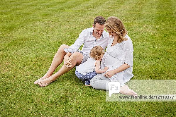 Ehepaar mit Tochter auf grünem Rasen