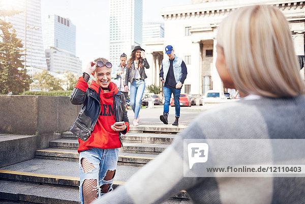 Zwei junge Freundinnen begrüßen sich in der Stadt