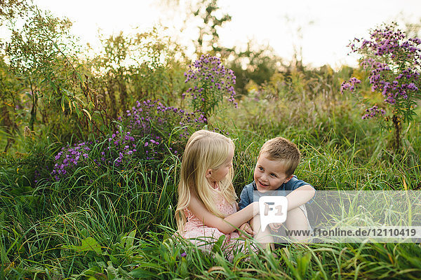 Boy and girl sitting in tall grass together