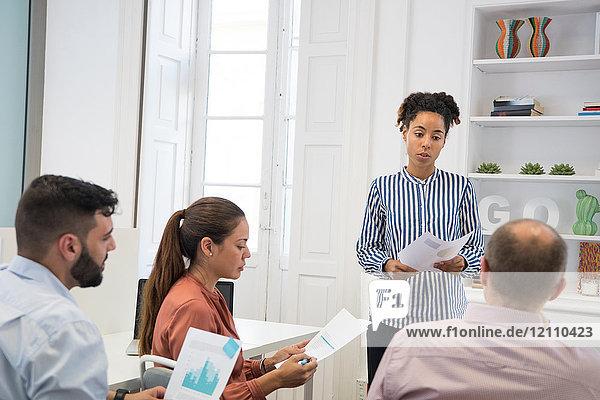 Geschäftsfrau macht Grafik-Präsentation am Tisch im Sitzungssaal