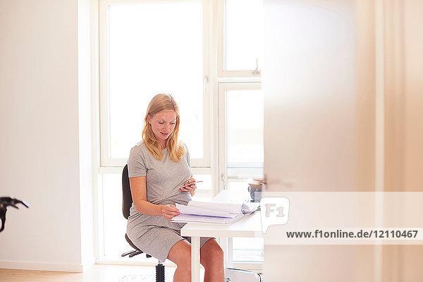 Schwangere junge Frau am Schreibtisch mit Blick auf Smartphone und Papierkram