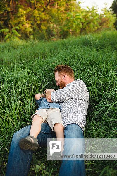 Vater kitzelt Sohn im hohen Gras