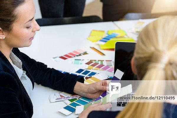 Junge Geschäftsfrauen betrachten Stoffmuster am Konferenztisch