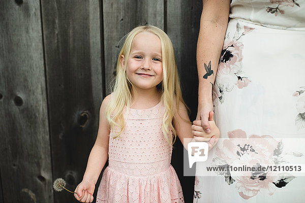 Portrait of girl holding dandelion clock and mother hand looking at camera smiling