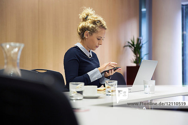 Woman in office texting on smartphone