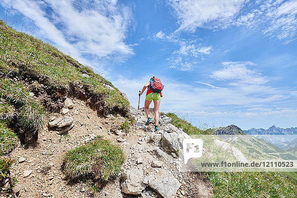 Rear view of female hiker hiking up Tannheim mountains  Tyrol  Austria